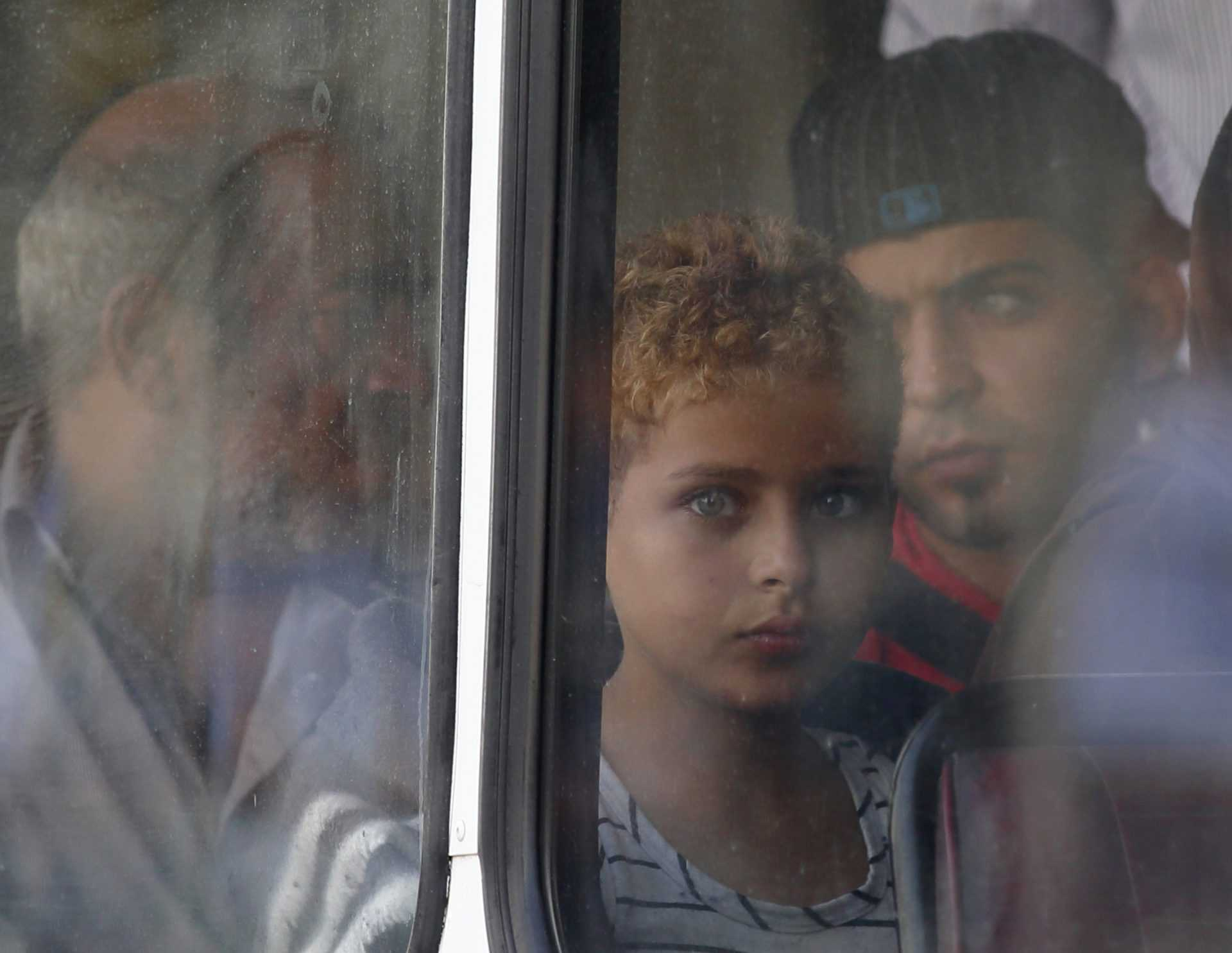 A rescued migrant child looks out of the window of a police bus after arriving at the Armed Forces of Malta Maritime Squadron base at Haywharf in Valletta's Marsamxett Harbour October 12, 2013. Dozens of people died on Friday when a boat carrying around 250 migrants capsized between Sicily and Tunisia, in the second such shipwreck this month, the Italian coastguard said. 147 survivors, believed to all be Syrians, arrived in Malta on Saturday morning, according to local media.  REUTERS/Darrin Zammit Lupi (MALTA - Tags: SOCIETY IMMIGRATION DISASTER) MALTA OUT. NO COMMERCIAL OR EDITORIAL SALES IN MALTA - RTX148LH
