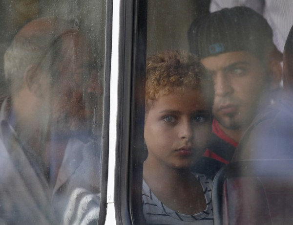 A rescued migrant child looks out of the window of a police bus after arriving at the Armed Forces of Malta Maritime Squadron base at Haywharf